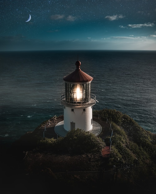 Beautiful aerial shot of a lit lighthouse on a green hill with the half-moon in the night sky Free Photo