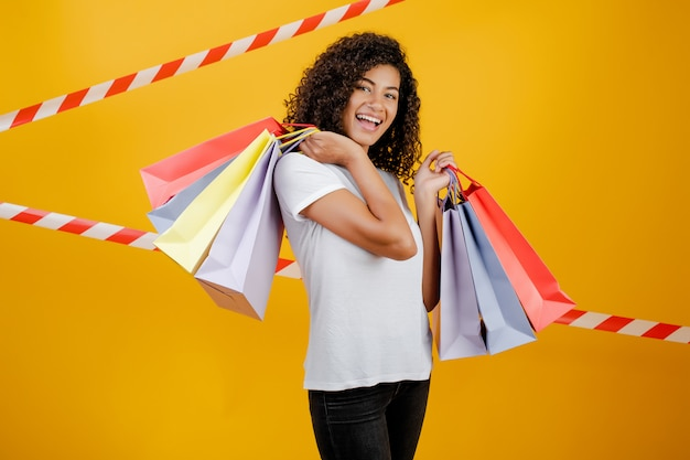 Beautiful african black woman with colorful shopping bags isolated over yellow with signal tape Premium Photo