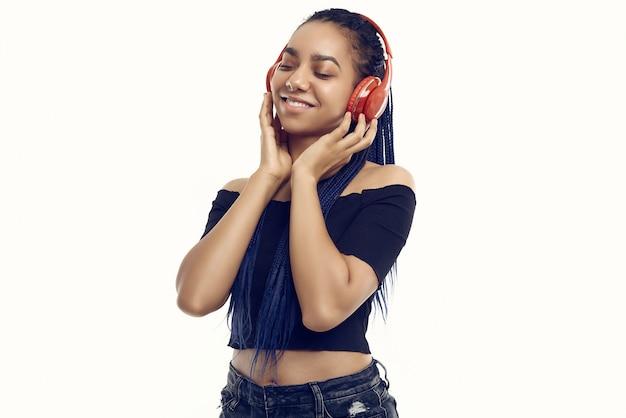 Beautiful african brunette teenage girl with dreadlocks listening music Premium Photo