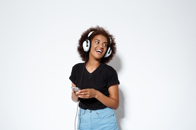 Beautiful african girl listening music in headphones over white wall Free Photo