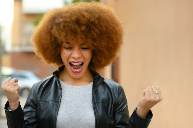 Beautiful african woman happy and excited celebrating victory expressing big success, power, energy and positive emotions. celebrates new job joyful, outdoor Premium Photo