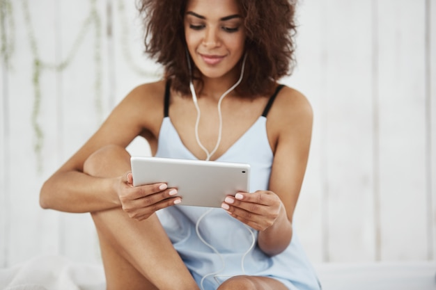 Beautiful african woman in sleepwear smiling looking at tablet listening to music in headphones sitting on bed. Free Photo