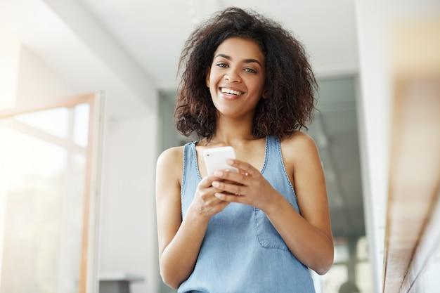 Красивая африканская женщина усмехаясь держащ телефон сидя в кафе. Бесплатные Фотографии