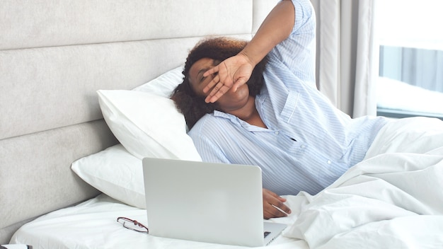 Beautiful african woman in stylish pajamas stretches while sitting in bed at home Premium Photo