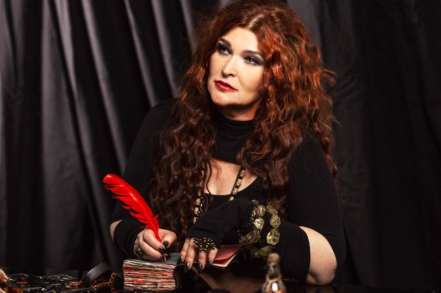 Beautiful aged redheaded woman fortune teller performs a magical ritual. Premium Photo