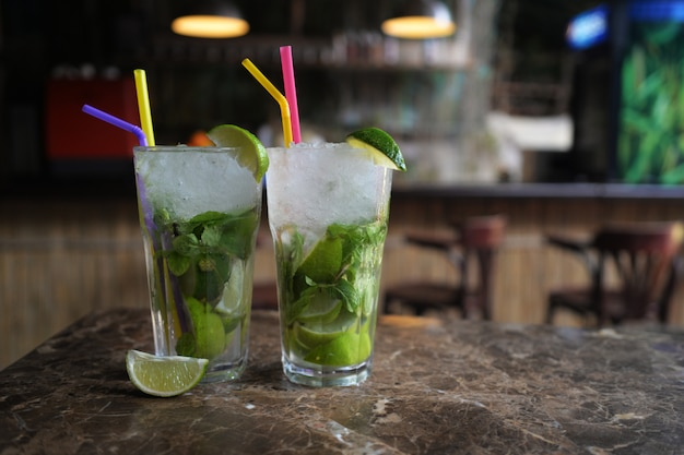 Beautiful alcoholic cocktails lime and mint mojito drinks at the bar Premium Photo