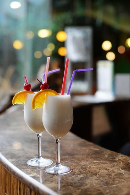 Beautiful alcoholic drinks cocktails with pineapple pinacolada and coconut on the bar counter Premium Photo