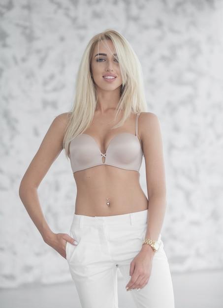 화이트 룸에서 포즈 베이지 색 란제리와 흰색 청바지에 아름 다운 매혹적인 젊은 여자 프리미엄 사진