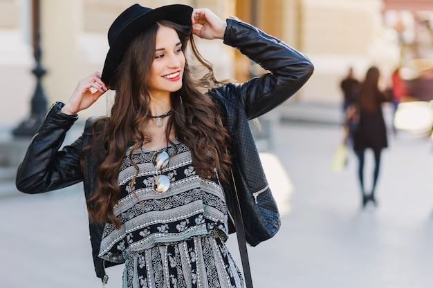 春や秋に長いウェーブのかかった髪型で美しい驚くべきブルネットの女性は、通りを歩いてスタイリッシュな都会の服。赤い唇、スリムなボディ。ストリートファッションのコンセプトです。 無料写真