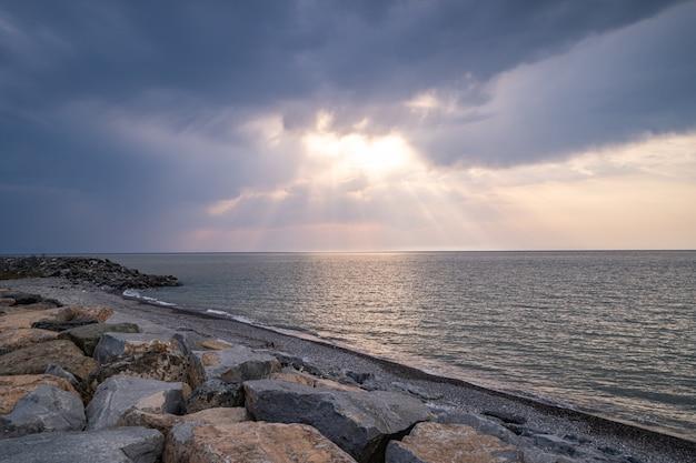 Красивые удивительные великолепные пейзажи скалистого берега, моря и пасмурного угрюмого неба с солнечными лучами Premium Фотографии