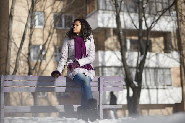 Beautiful american black female in the street winter sitting on a bench Free Photo