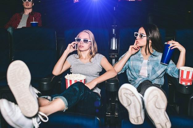 美しく魅力的な女の子が椅子に座っています。ブロンドの女の子が電話で話しています。彼女の友人は沈黙のシンボルを見せています。彼女は静かになり、映画を見ている間話をやめたいと思っています。 Premium写真