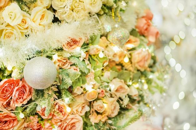 バラと美しく明るいクリスマスツリー Premium写真