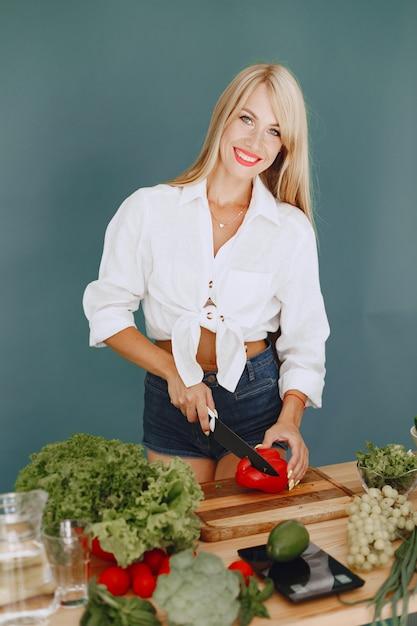 野菜とキッチンで美しくスポーティな女の子 無料写真
