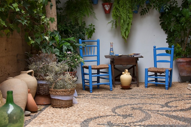 Красивый андалузский дворик с растениями, голубыми стульями, деревянным столом и вазами на мозаичном каменном полу. кордова, андалусия, испания. Premium Фотографии