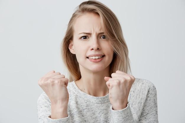 何気なく身なりをした美しい怒りの猛烈なヨーロッパの女性は不満に顔を眉をひそめ、拳を握り締め、自分自身を守り戦う準備ができており、気分を害します。否定的な感情 無料写真