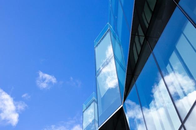 아름 다운 건축 비즈니스 사무실 마천루 도시에서 창 유리 패턴으로 건물. 구름은 건물의 유리 파사드에 반영됩니다. 프리미엄 사진