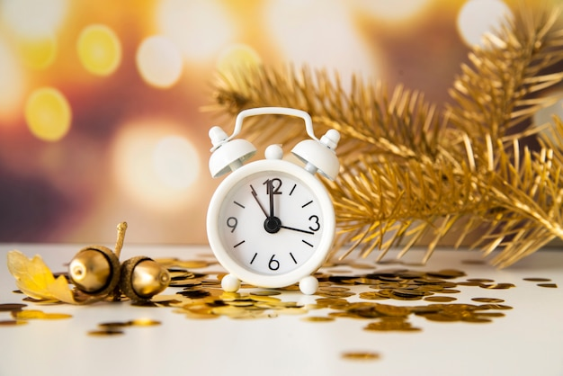 Beautiful arrangement with clock showing midnight and pine trees Free Photo