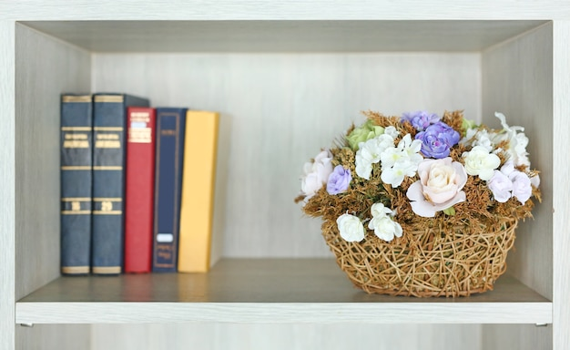 Beautiful Artificial Flower In Basket On The Bookshelf Library Premium Photo