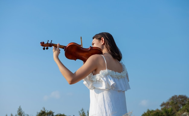 Beautiful asia girl white dress playing on a violin Premium Photo