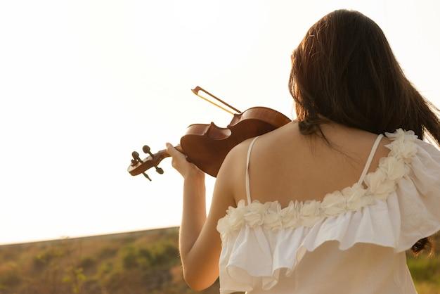 Beautiful asia girl white dress playing on a violin Premium Photo