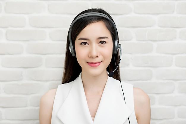 Beautiful asian businesswoman wearing microphone headset  as a telemarketing customer service agent Premium Photo