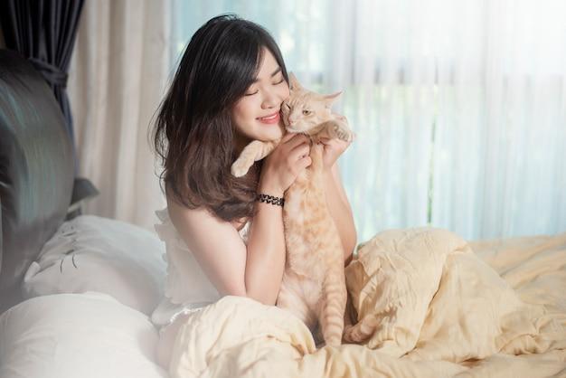 美しいアジアの猫の恋人の女性は彼女の部屋で猫と遊んでいます Premium写真