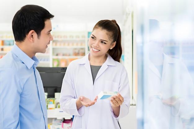 Beautiful asian female pharmacist  with customer in a pharmacy. Premium Photo