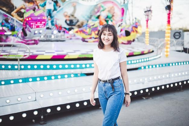 Красивая азиатская девушка в парке развлечений Premium Фотографии