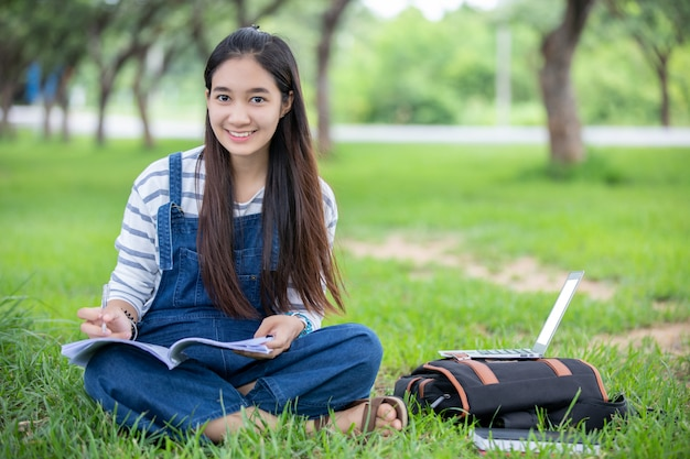 Beautiful asian girl student holding books and smiling  and learning and education   on park in summer for relax time Premium Photo