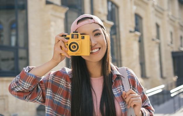 Premium Photo | Beautiful asian girl taking photo on retro camera
