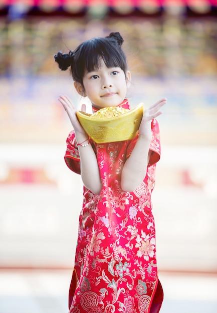 Красивая азиатская девушка носит красный чонсам и держит китайский золотой слиток перед мраморными ступенями красивого китайского храма на китайский новый год Premium Фотографии