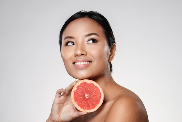 Beautiful asian lady looking aside and holding grapefruit slice near face Free Photo