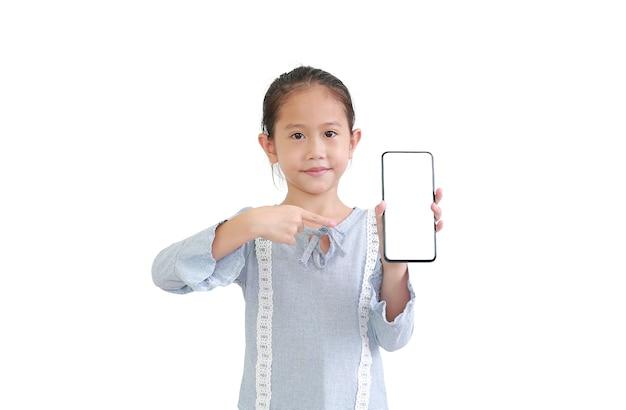 Красивый азиатский маленький ребенок держит смартфон и указывает на пустой белый экран Premium Фотографии