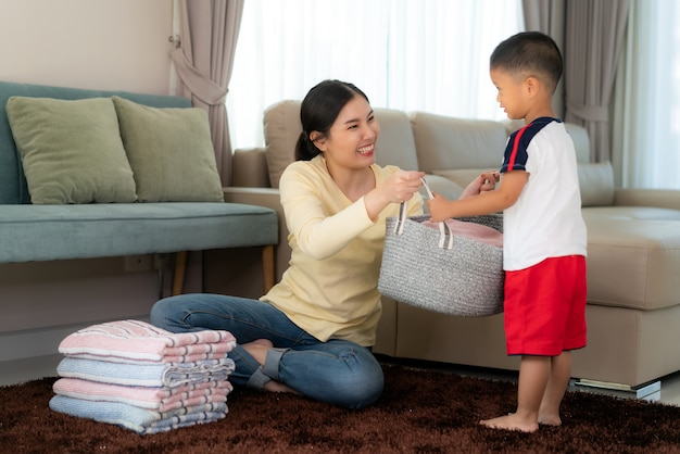 Beautiful asian mother and child boy little helper are having fun and smiling while doing help her mother folded clothes laundry at home. happy family. Premium Photo