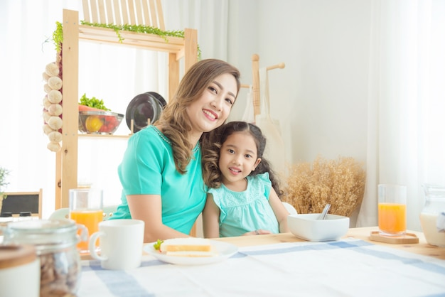 Beautiful asian mother and daughter having breakfast together at home in the morning Premium Photo