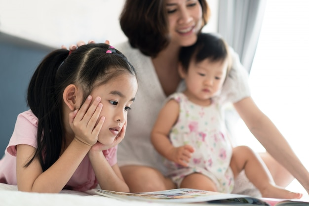 Beautiful asian mother reading fairly tale story book with her children on the bed. Premium Photo