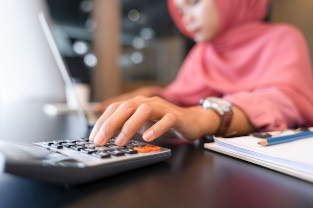Beautiful asian muslim business woman in pink hijab and casual wear working with calculator Premium Photo