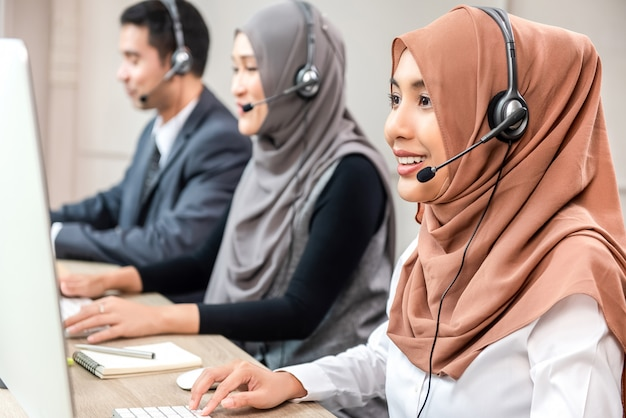 Beautiful asian muslim woman working  in call center with team Premium Photo