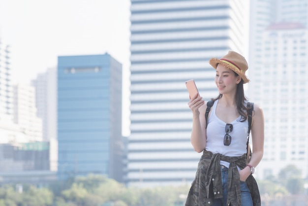 Beautiful asian solo tourist woman smiling and looking at mobile phone Premium Photo