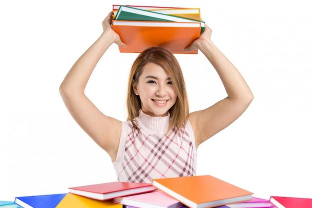 Красивая азиатская девушка студента держа книги Premium Фотографии