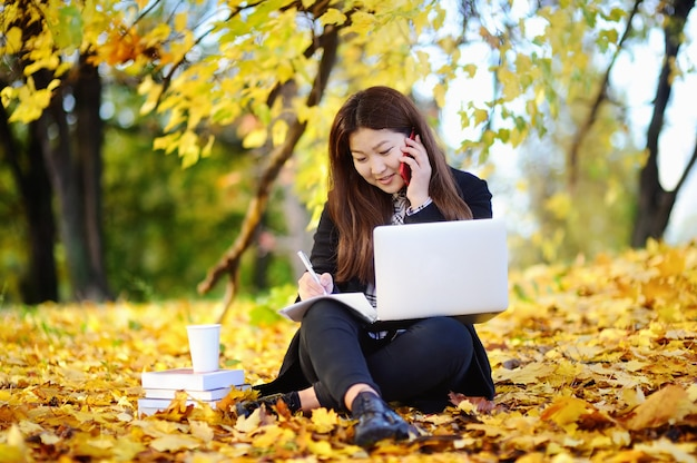 Beautiful asian student girl outdoors portrait. young woman studying/working and enjoying beautiful sunny autumn day Premium Photo