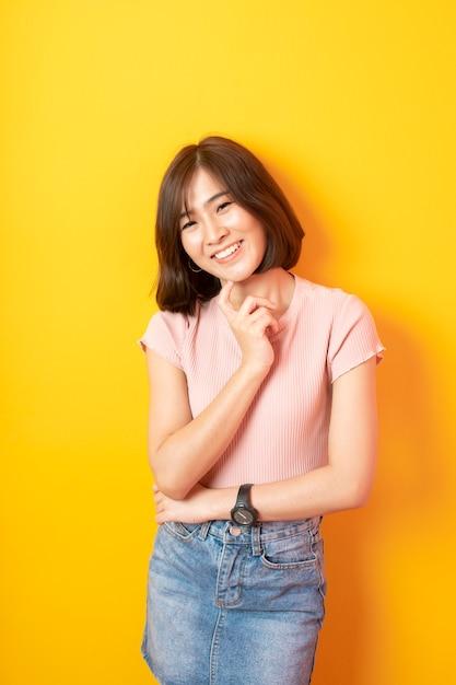 Beautiful asian student happy on yellow wall Premium Photo