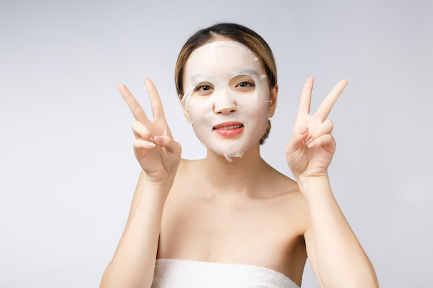 Premium Photo | Beautiful asian woman applying paper sheet mask on her face  white background.