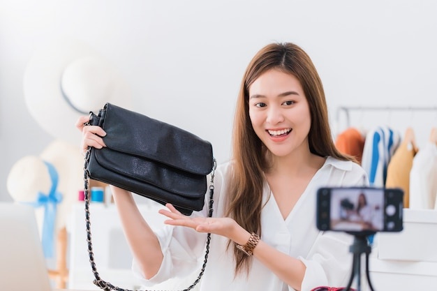 Beautiful asian woman blogger is showing and review product.in front of the smartphone camera. Premium Photo