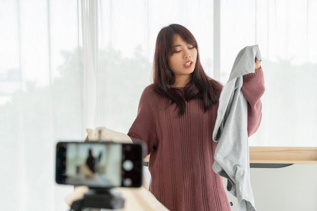 彼女の店でライブvlogを記録するカメラに服を見せて美しいアジアの女性ブロガー Premium写真