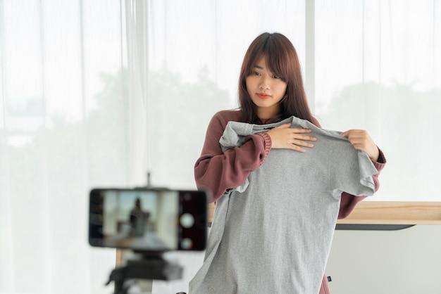 彼女の店でvlogビデオライブストリーミングを記録するためにカメラに服を示す美しいアジアの女性ブロガー Premium写真