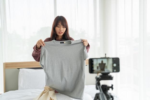 Vlogビデオを記録するカメラに服を示す美しいアジアの女性ブロガー Premium写真