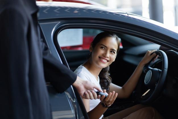 Bella donna asiatica che compra un'auto presso lo showroom Foto Gratuite