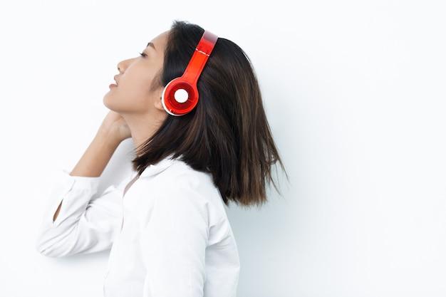 Beautiful asian woman enjoying listening to music Free Photo
